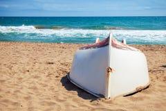 Stara biała łódź kłaść na piaskowatej plaży Zdjęcie Royalty Free