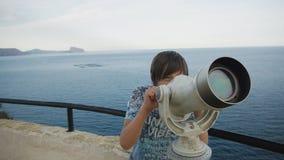 Stara chłopiec patrzeje dennego brzeg w teleskop od wysokiego podwyższonego obserwacja pokładu zbiory