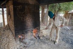 Stara chłopiec tonie i koryguje ogienia, okopcony, piekarniku, umieszczać drewno Zdjęcia Royalty Free