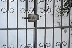 Stara czarna ogrodowa brama w śniegu Zdjęcia Stock