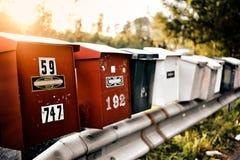 Stara czerwona skrzynka pocztowa z liczbami z światłem słonecznym i drzewami w tle w Szwecja z rzędu Obraz Stock