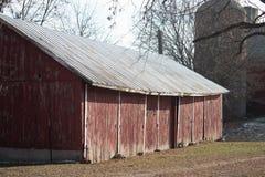 Stara czerwona stajnia z silosem na gospodarstwie rolnym w opóźnionej jesieni na słonecznym dniu zdjęcia royalty free