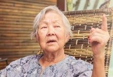 Stara dama mówi opowieści Poważny wyrażenie z palcem up obrazy stock