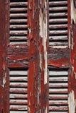 Stara drewniana żaluzja z czerwoną obieranie farbą obraz stock