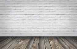 Stara drewniana podłoga z białą cegły ścianą Zdjęcia Royalty Free