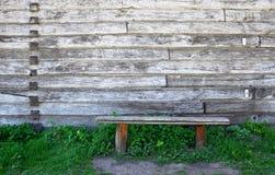 Stara drewnianej ławki pozycja w trawie przeciw tłu drewniana ściana zdjęcie stock