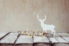 Stara drzewna bela z czarodziejskimi bożonarodzeniowe światła i reniferem na drewnianym stole Selekcyjna ostrość zdjęcia stock