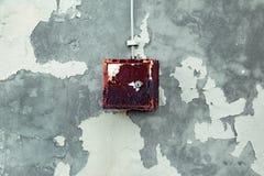 Stara elektryczna osłona wiesza na exfoliating ścianie dom, ośniedziały metalu pudełka obwieszenie na ścianie Obrazy Royalty Free