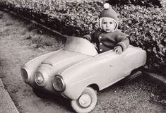 Stara fotografia dziewczyna w zabawkarskim samochodzie troszkę Zdjęcia Royalty Free