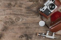 Stara fotografii kamera, obiektyw nakrętka, tripod i brown przewożenie skrzynka na drewnianym tle, Obraz Royalty Free