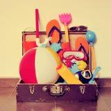 Stara kartonowa walizka pełno plażowe rzeczy z retro skutkiem, Obrazy Stock