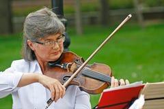 Stara kobieta bawić się skrzypce w ulicie w miasto dniu w Volgograd Zdjęcia Royalty Free