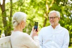 Stara kobieta fotografuje mężczyzna smartphone w parku Zdjęcie Royalty Free