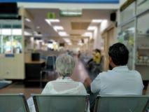 Stara kobieta i dorosły mężczyzna siedzimy na szarym nierdzewnym krzesła czekaniu medycznym szpital i zdrowie usługa zdjęcie royalty free