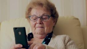 Stara kobieta i jej nowy smartphone zdjęcie wideo