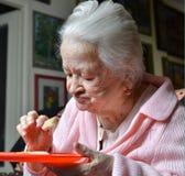 Stara kobieta je plasterek chleb obrazy royalty free
