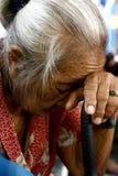Stara kobieta odpoczywa jej głowę na jej trzcinie Zdjęcia Royalty Free