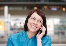 Stara kobieta ono uśmiecha się gdy opowiadający na telefonie komórkowym Zdjęcie Royalty Free