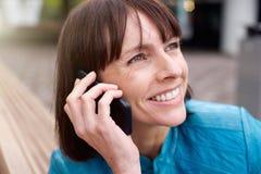 Stara kobieta ono uśmiecha się z telefonem komórkowym outside Obrazy Stock