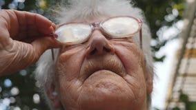 Stara kobieta prostuje jej szkła i patrzeć naprzód Portret plenerowy babcia Babcia jest ubranym eyeglasses zbiory