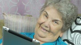 Stara kobieta relaksuje używać pastylka komputer zbiory