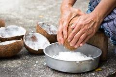 Stara kobieta siedzi na kokosowym grater i kratownicy koksie fotografia royalty free