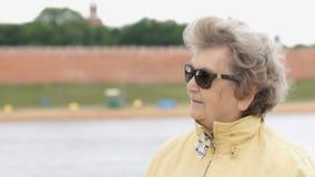 Stara kobieta starzał się 80s w ciemnych szkieł spojrzeniach popierać kogoś zdjęcie wideo