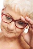 Stara kobieta trzyma jej głowę, thinking/martwić się. Fotografia Stock