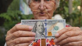 Stara kobieta w eyeglasses seansu rachunku sto dolarów w kamerę i ono uśmiecha się plenerowy Babci mienia gotówka outside zdjęcie wideo