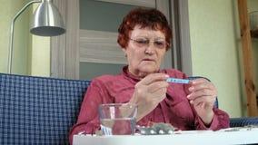 Stara kobieta z gorączkowym sprawdza rtęć termometrem zdjęcie wideo