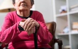 Stara kobieta z jej rękami na trzcinie obraz royalty free