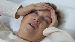 Stara kobieta z migrena bólu lying on the beach w łóżku, migrena wprowadza nieporządek, problem zdrowotny zdjęcie wideo