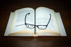 Stara książka otwarta i eyeglasses Obrazy Royalty Free
