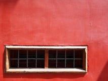 Stara malująca czerwona betonowa ściana z wąskim bielem obramiał okno Fotografia Stock