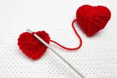 Stara metalu szydełkowania haczyka i czerwieni przędzy piłka jak serce na białym szydełkowym tle Handmade szydełkująca wełny orga Obrazy Royalty Free