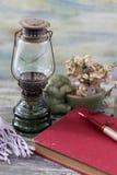 Stara nafciana lampa na drewnianym stole, książkowy i ceramiczny obraz royalty free