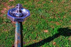 Stara, nieociosana, wodna fontanna z trawiastym tłem, obrazy stock