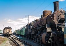 Stara ośniedziała parowa lokomotywa obok stacji kolejowej platformy retro pociąg obraz royalty free