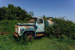 Stara ośniedziała przerastająca ciężarówka Zaniechany Radziecki cysternowy samochód w miasto widmo zdjęcie stock