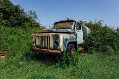 Stara ośniedziała przerastająca ciężarówka Zaniechany Radziecki cysternowy samochód w miasto widmo fotografia stock