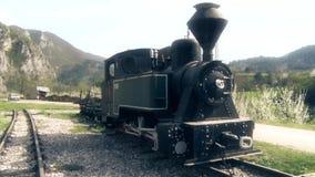 Stara parowa lokomotywa przy stacją kolejową zbiory