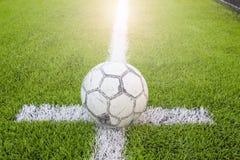 Stara piłka w bielu z czernią akcentuje na sztucznej murawie Zdjęcie Royalty Free