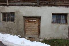 Stara popielata stajni fasada z wykonującymi ręcznie drzwiowymi i kraciastymi okno w terenie górskim Obraz Royalty Free