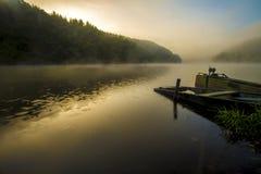 Stara przyglądająca mała łódka na jeziorze przy wschodu słońca czasem z mgłą obrazy royalty free