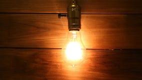 Stara rocznika Edison żarówka jarzy się na tle drewniane deski stopniowo zaświeca up i iść out zbiory