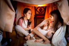 Stara siostra mówi straszną opowieść młody jeden przy nocnym Zdjęcie Royalty Free