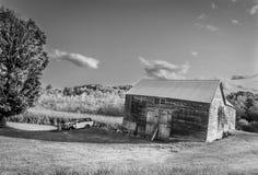 Stara stajnia, garaż i samochód w śródpolny czarny i biały, fotografia royalty free