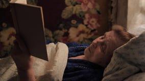 Stara starsza kobieta kłama w łóżku pod czytaniem i koc książka zbiory wideo