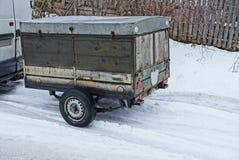 Stara szara drewniana przyczepa z czernią toczy na białym śniegu na drodze zdjęcia stock