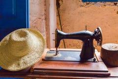 Stara szwalna maszyna i słomiany kapelusz Obrazy Stock